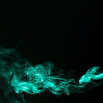Abstract fragment movement of green smoke on black background