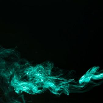 검은 배경에 녹색 연기의 추상 조각 운동