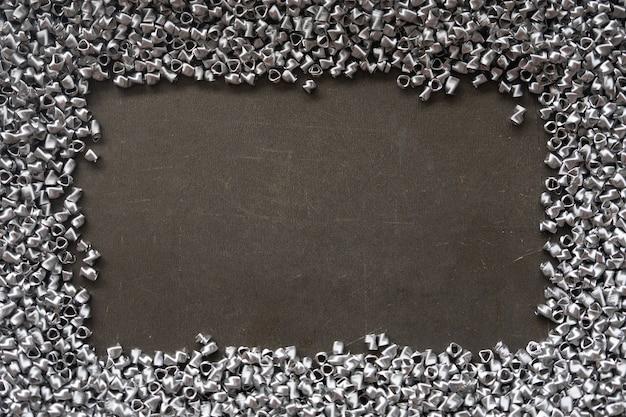 テキストのための場所が付いているステンレス製の金属ばねから成っている抽象的なフレーム。