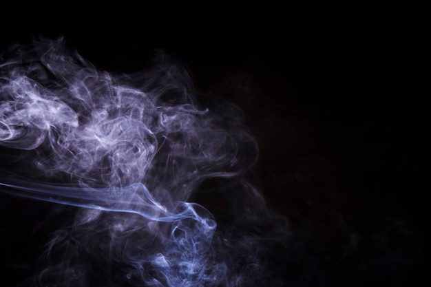 Abstract fumes of smoke against black background