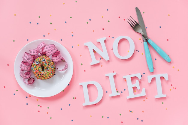 Abstract funny face of woman from donut with eyes and hair from centimeter tape on plate, cutlery and text no diet
