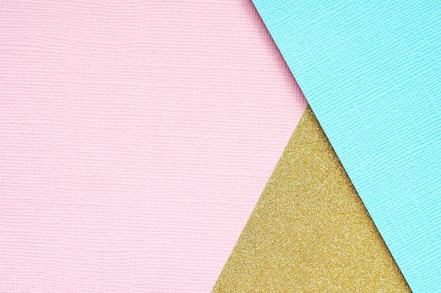 金、青、ピンクの紙の抽象的な幾何学的な背景。