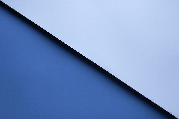 影で互いの上に横たわっている2つの青い紙片の抽象的な幾何学的な背景。