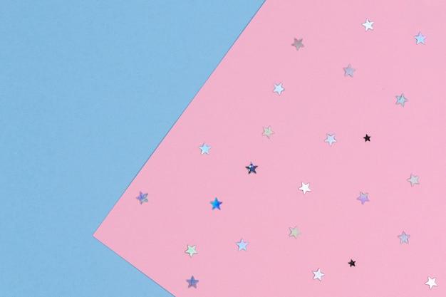 抽象的な幾何学的なお祭りの背景。キラキラ星と紙の背景と水色とパステルピンク。上面図
