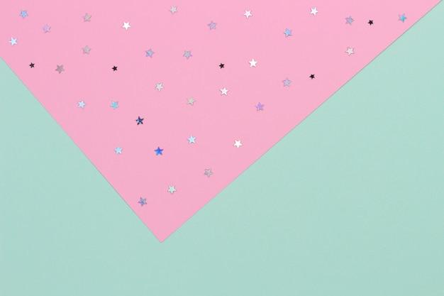 抽象的な幾何学的なお祭りの背景。薄緑とパステルピンクのキラキラ星紙の背景。上面図