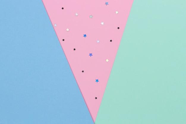 キラキラ星と抽象的な幾何学的なお祝いパステルカラーの用紙の背景。上面図