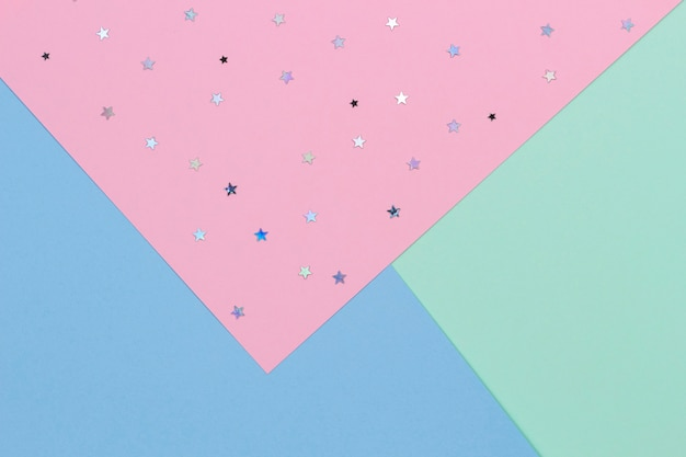 Abstract geometric festive pastel color paper background with glitter stars top view