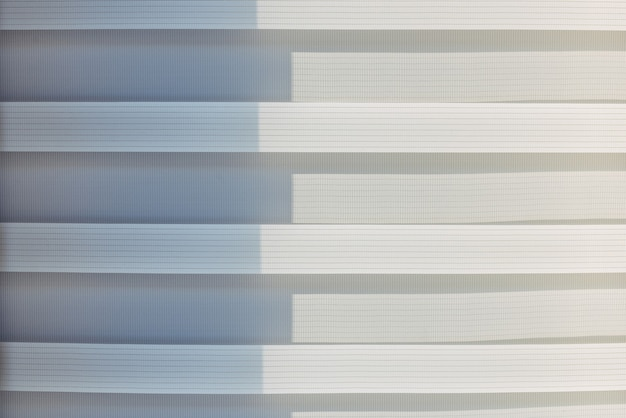 白とグレーのグラデーションカラーの抽象的な幾何学的な水平線。繰り返しパターン、背景の質感、縞模様のデザイン。太陽に照らされたローラーブラインド、クローズアップ。