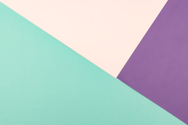 Abstract geometric paper background of pastel pink, blue and purple colors.