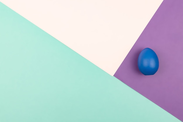 Abstract geometric paper background of pastel pink and purple colors with blue easter egg. copy space for design.