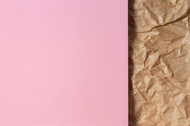 Abstract geometric paper texture background blank light pink color paper sheet over recycle crumpled brown paper background