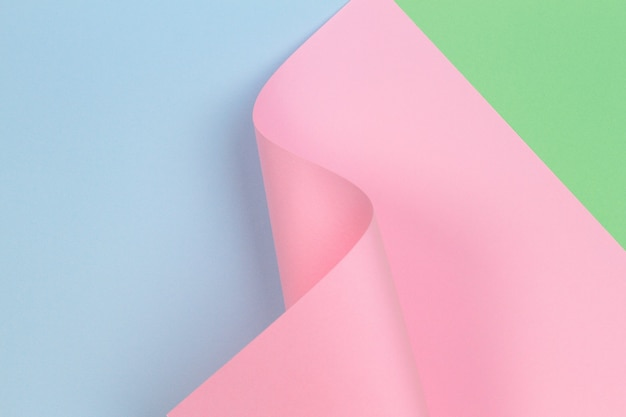Abstract geometric pink paper shape on blue and green color paper wall