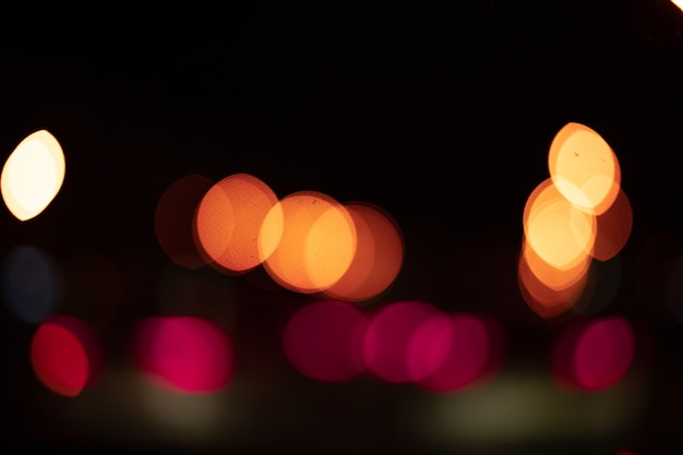 Abstract glare of light with bokeh in blur on a black background. texture,night city lights and cars in blur.