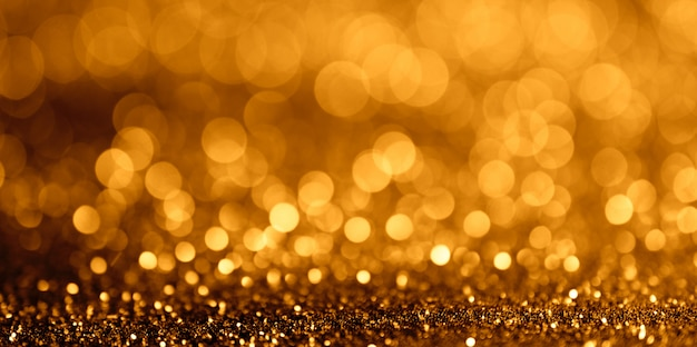 Abstract glitter bokeh light on golden background wide fan page panorama format.