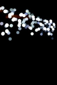 추상 반짝이 스파클 보케는 검정색 배경에 초점을 맞췄습니다. 배경에 많은 둥근 빛.