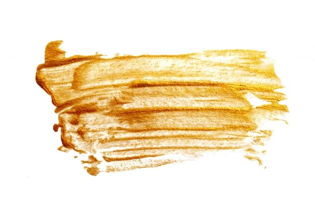 白い背景の上のアクリルペイントブラシと抽象的な金背景