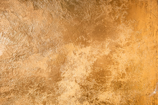 Abstract gold texture. wall colored with golden plaster.