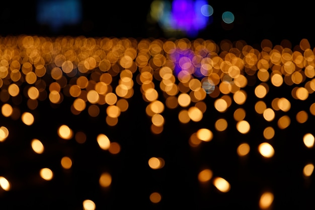 Abstract golden bokeh from candle light on black background.