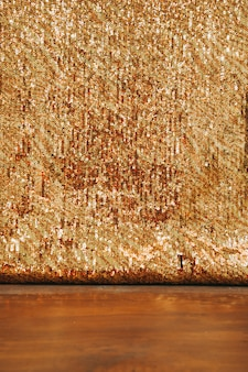 Abstract golden glitter backdrop on wooden desk