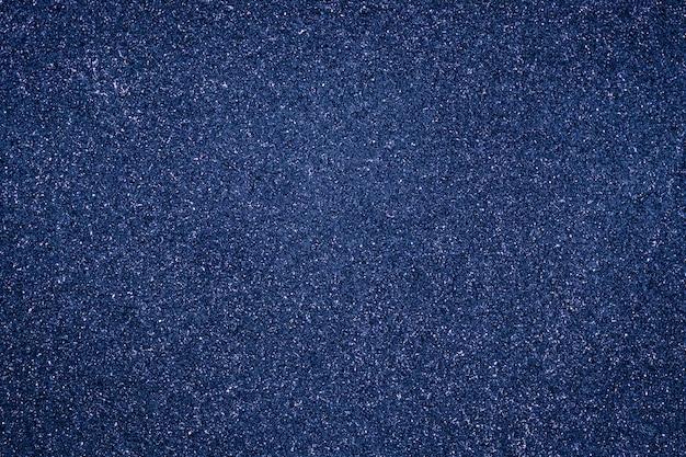 抽象的な穀物の背景、濃い青の粒状のテクスチャ。グランジ壁の光沢のある表面。