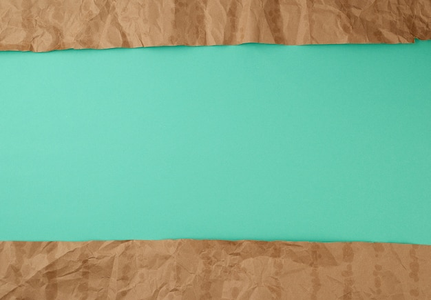 Abstract green surface with brown torn paper elements