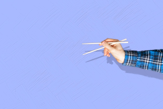 The abstract hand holding the empty pair of wooden chopsticks isolated on color background,