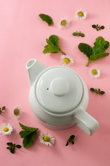 Abstract herbal tea with fresh chamomile flowers and mint leaves, top view