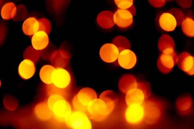 ぼやけたボケ味の抽象的な休日の背景黒の背景に金色のライト