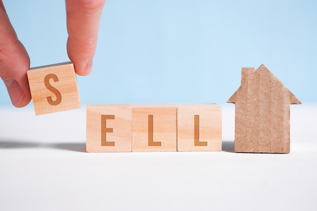 Abstract house made of cardboard hand holds with wooden cubes with the word sell. home sale .