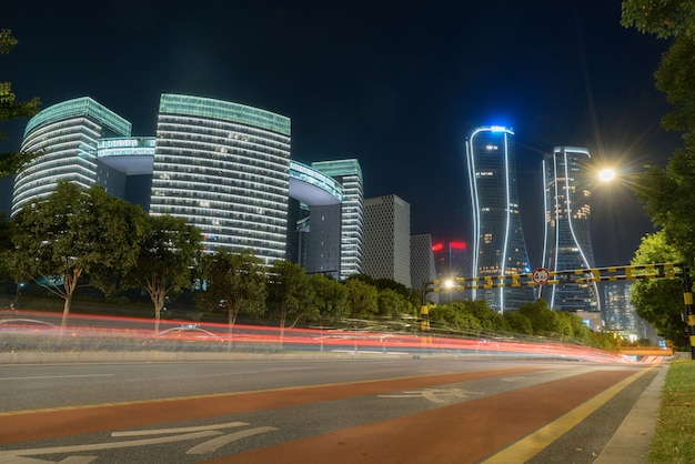 Abstract image of blur motion of cars on the city road at night, modern urban architecture