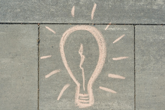 Abstract image drawing of light bulb written on grey sidewalk