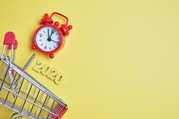 トロリーと黄色の背景の時計の横にある木製の文字の2020年の抽象的なイメージ。消費の概念。コピースペース。