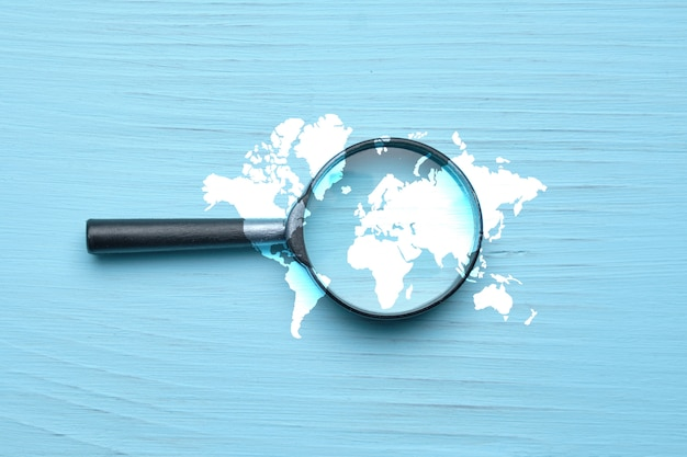Abstract image of a world search with magnifier on a wooden background.
