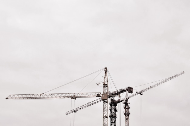 Abstract industrial background with construction tower cranes