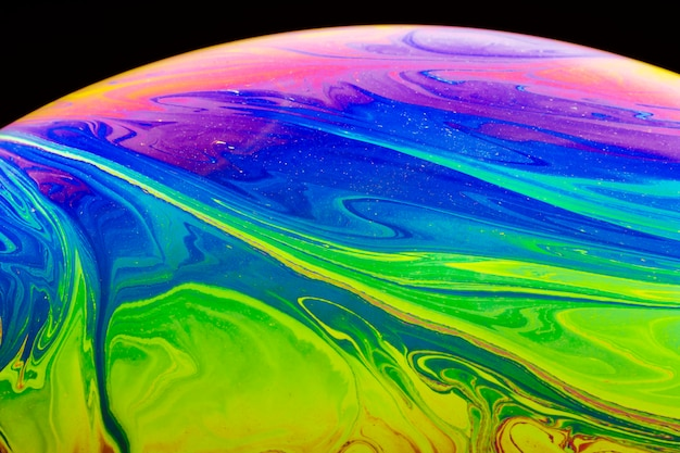 黒の背景に抽象的な虹色のシャボン玉