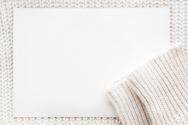 Abstract knitted background with clear paper. white woolen sweater with sleeves.