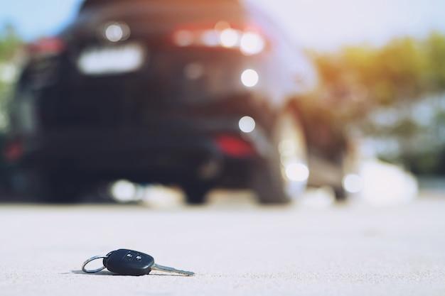 抽象的な失われた車の鍵は、通りのコンクリートセメント地面道路の家の前庭に横たわって落ちる。