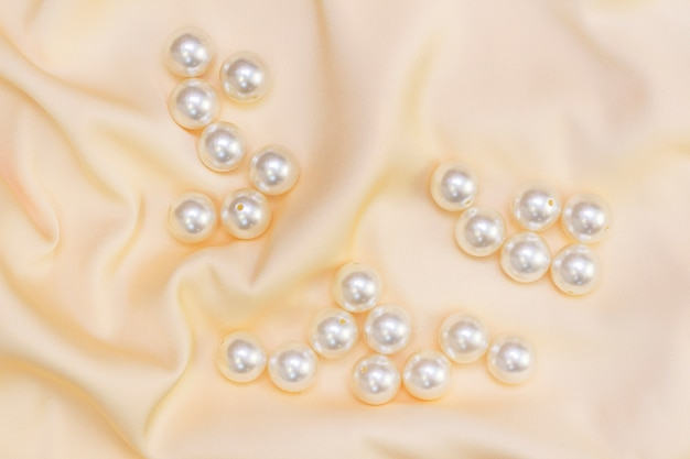 Abstract luxury fabric with pearl beads. silk natural fabric. silk golden beige fabric texture with pearls.