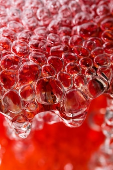 強力な流れの中の抽象的なマクロ撮影の水は、気泡の形成で赤い花瓶を満たします