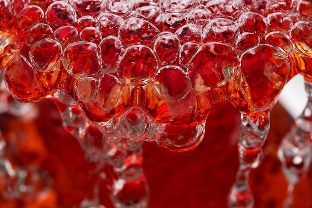 Abstract macro photography water in a powerful stream fills a red vase with the formation of air bubbles