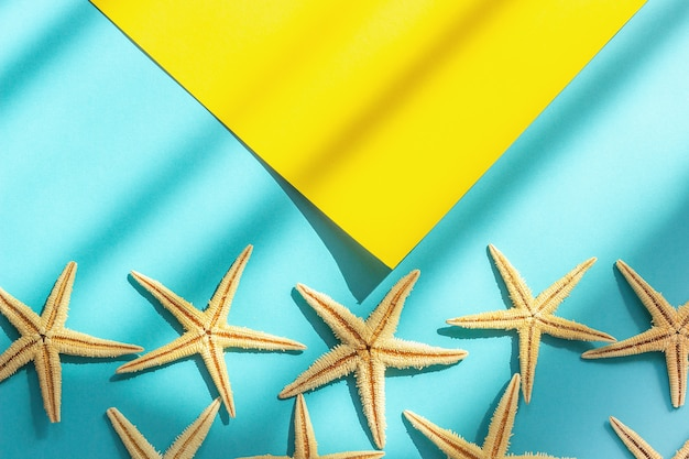Abstract marine sea background. yellow and blue paper background with starfishes, hard light and shadow