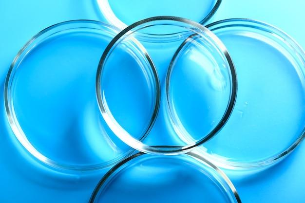 Абстрактная медицинская косметология синий фон из стеклянных чашек петри.