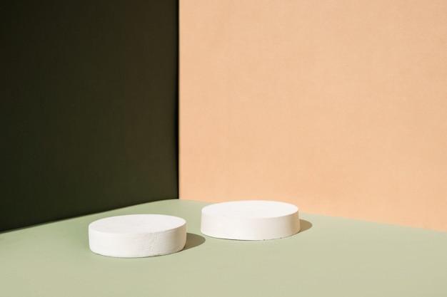緑とベージュの背景のabstracに幾何学的な形のシリンダー表彰台を持つ抽象的な最小限のシーン...