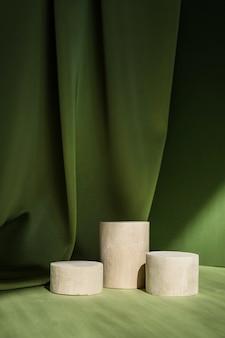 緑の表面に幾何学的な形のシリンダー表彰台を持つ抽象的な最小限のシーン