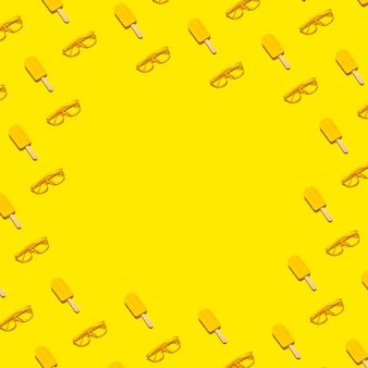 Abstract minimal summer flat lay border frame of yellow popsicles and sunglasses on abstract vivid background with copy space