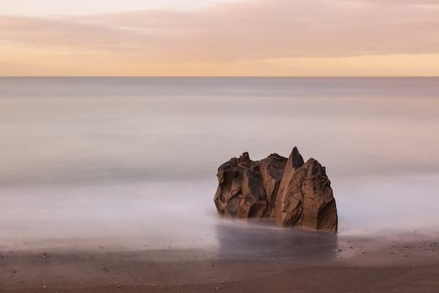 전경에 외로운 바위와 주위에 유백색 흐린 바닷물을 보여주는 일출 이른 아침에 추상 미니멀 긴 노출 바다