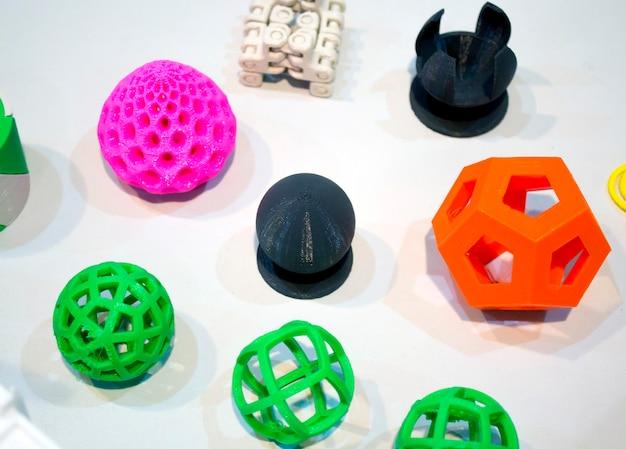 3d 프린터 클로즈업으로 인쇄된 추상 모델. 흰색 테이블에 3d 프린터로 인쇄된 밝고 다채로운 물체. 진보적인 현대적 적층 기술. 4.0 산업혁명의 개념