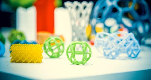 Абстрактные модели напечатаны крупным планом на 3d принтере. яркие красочные объекты, напечатанные на 3d-принтере на белом столе. прогрессивные современные аддитивные технологии. концепция 4.0 промышленной революции
