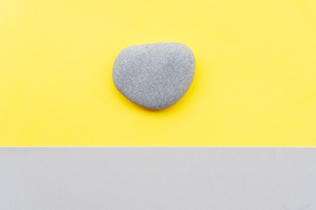 Abstract modern handmade paper background with a stone in ultimate gray and illuminating yellow colors