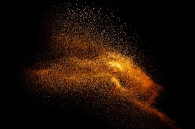 抽象化された運動には、茶色の砂の背景がぼやけています。暗い背景上に分離された砂質の爆発。